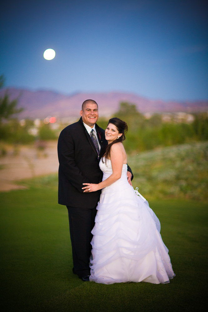 Bride and Groom with moon in background at magic hour on golf course