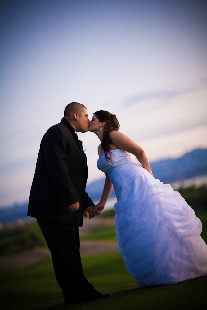 Sunset photograph of bride and groom kissing with golf course and lake in background